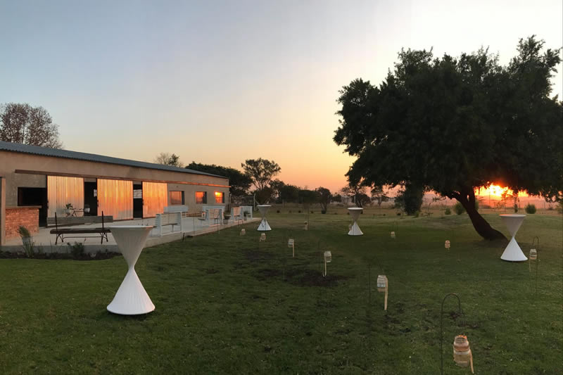 outside a barn with tables and lights at sunset